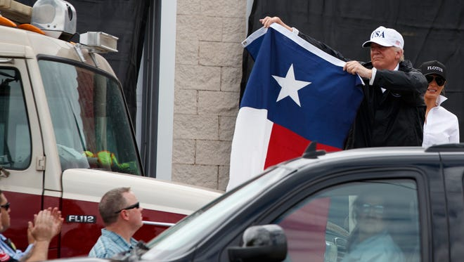 President Trump holds up a Texas flag after speaking with supporters outside a firehouse in Corpus Christi, Tex. on Tuesday, following a briefing on Harvey relief efforts.