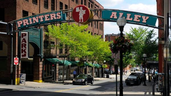The Printers Alley sign crosses Church Street  in Nashville. Several businesses along Printers Alley — The Brass Stables, Lonnie's Western Room and Fiddle & Steel Guitar Bar — might have to move for a proposed boutique hotel.