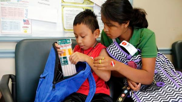 Second-grader Alex Galicia, 7, and sixth-grader Dulce Garcia, 12, look at the supplies in the new backpacks they received from People to People's Back to School with Dignity program on Aug. 14 in Nanuet.