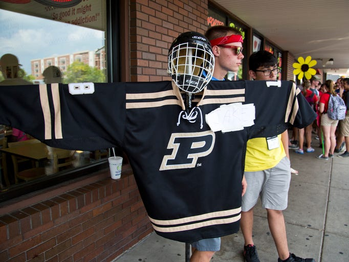 Purdue University sophomore Jake Van Vuren holds his beacon made of a Purdue hockey shirt and mask so incoming freshman at Boiler Gold Rush can follow him Monday, August 18, 2014, near campus in West Lafayette. The new students were touring the village area near the campus.