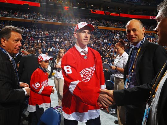 Filip Hronek shakes hands with Red Wings officials