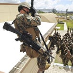 Members of the 3rd Battalion 6th Marines participate in a fast-rope training exercise at the Explosive Ordnance Disposal Mobil Unit Five rappelling tower on Naval Base Guam on March 5.