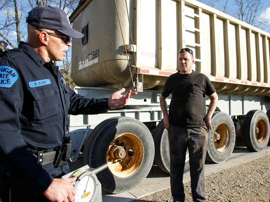 Michigan State Police motor carrier Sgt. Brett Black, left, discusses the challenges of Michigan's weight laws with Ryan Hendrickson, owner of Hendrickson Trucking Co., center, and driver Ron Sexton, right, on Nov. 4, 2015.