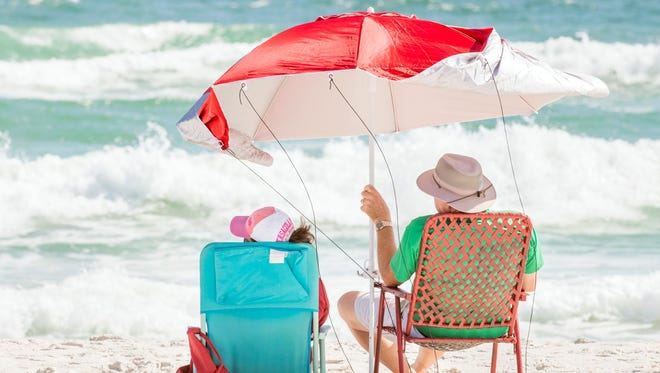 John Buford, of Guntersville, Alabama, holds on to his umbrella in strong wind Oct. 4, 2017, as he and his wife, Kathleen, watch the rough surf at Pensacola Beach, Florida