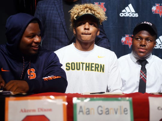 Vero Beach High School's Akeem Dixon (from left), Alan Glanville and Cameron Hicks sit at the table with 11 other football teammates Wednesday, Feb. 7, 2018, as the group prepares to sign their letters of intent to play football at the collegiate level on National Signing Day. Dixon will play for Syracuse, Glanville is heading to Missouri Southern and Hicks signed with Alabama A&M University.