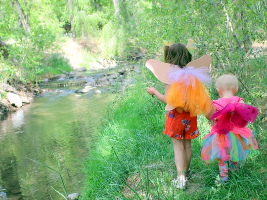Dressed for the exploration, Ammelia Cherry, right, and Clara Sherrell explore the banks of the Rio Ruidoso looking for fairy houses.