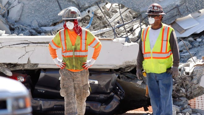 Workers stand in front of crushed cars under a section of a collapsed pedestrian bridge, Friday, March 16, 2018 near Florida International University in the Miami area. The new pedestrian bridge that was under construction collapsed onto a busy Miami highway Thursday afternoon, crushing vehicles beneath massive slabs of concrete and steel, killing and injuring several people, authorities said.