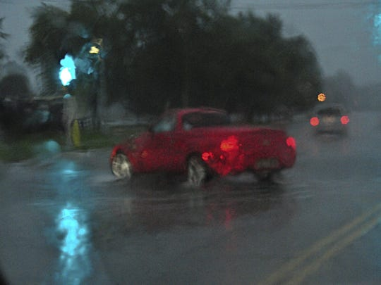 Drivers negotiate flooded areas of Egg Harbor Road in Sturgeon Bay on Thursday evening.