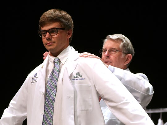 Forrest Ericksen is coated during the Medical College of Wisconsin Central Wisconsin White Coat Ceremony at UW Marathon County, in Wausau, Wisconsin, July 7, 2016.