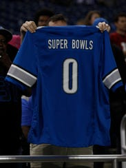A fan holds up a Lions jersey after the team's 42-17