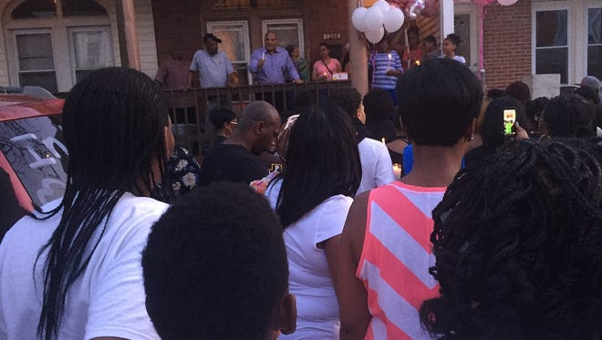 Balloons flutter as Pastor Amir Khan addresses a vigil outside the home of a young accident victim in Parkside.