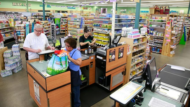 Rena Yazzie, center, checks out Dusty Hoefer at Natural Grocers on Saturday in Farmington.