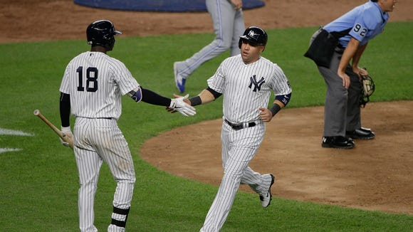 New York Yankees' Carlos Beltran, right, is greeted by Didi Gregorius after scoring on a sacrifice fly by Chase Headley against the Toronto Blue Jays during the eighth inning of a baseball game, Tuesday, May 24, 2016, in New York. The Yankees won 6-0.