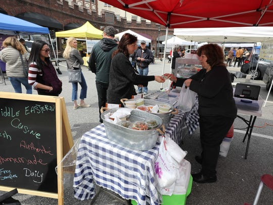 Amal Suleiman, with the Irvington Delight middle eastern cuisine shop, makes a sale during the Scarsdale's farmers market at the village green, April 12, 2018.