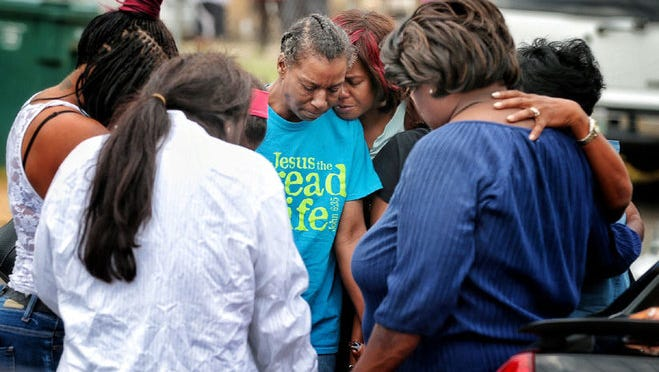 Family members gather outside the scene of a fatal fire early Monday morning that killed nine people, including five children.