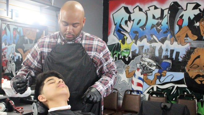 Barber Daveon McGary gives a young patron a haircut at his shop on London Street. McGary, 27, says that he sees a lot of young men coming in that feel lost and he wants to help.