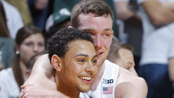 Bryn Forbes, left, and Matt Costello watch from the bench during the closing moments of MSU's  senior day victory over Ohio State on March 5. The two Spartans were named to the all-tournament team at the Portsmouth Invitational Tournament over the weekend.
