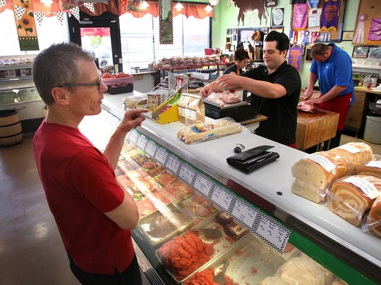 A customer of Kincaid's Meat Market since 1982, Kevin McGuinness keeps the butchers busy May 16, 2012, with his order. They are Loreal Gavin, Jonathan Dugdale and James Jennings.