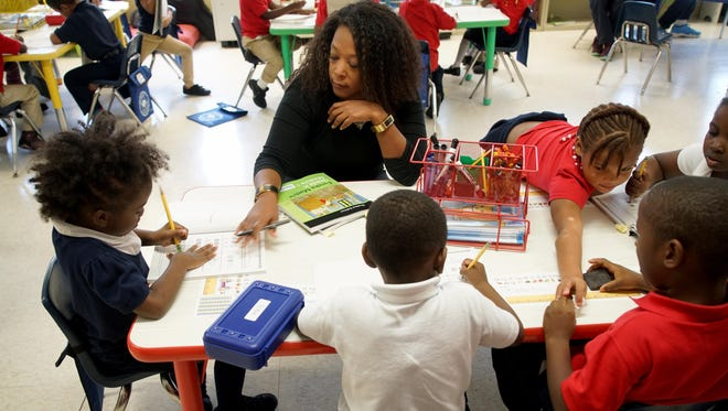 Donna Faber, a kindergarten assistant teacher at Thomas Edison Charter School, helps 5-year-old Lon'nae French with math work during class on Tuesday. Fifteen charter schools were suing the Christina School District and the state Department of Education over funding.