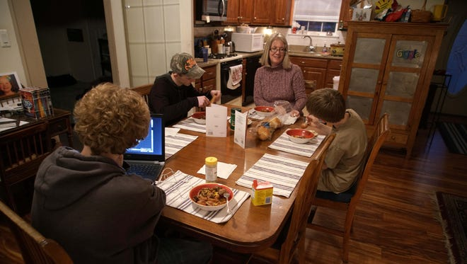 Pat eats dinner with her three grandsons who she has been raising since the courts awarded her full custody after her son and daughter-in-law could not properly care for them because of a heroin addiction.