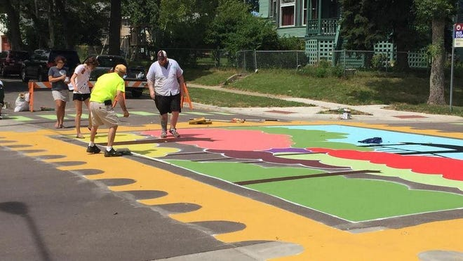 Residents paint a street mural at 15th Street and Second Avenue on Saturday.