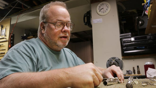 Instrument repairman Jeff Schieble works on a flute at his home workshop in Sheboygan.