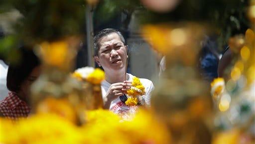 A man prays at the Erawan Shrine at Rajprasong intersection, the scene of last week's bombing, in Bangkok, Thailand, on Monday, Aug. 24, 2015.
