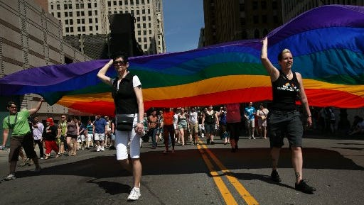 Motor City Pride volunteers carry a giant rainbow flag during the parade in Detroit, Mich, in 2011.