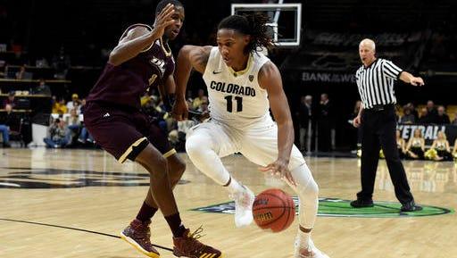 Colorado's Xavier Johnson dribbles past ULM's Travis Munnings during an NCAA college basketball game Thursday night.