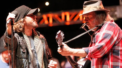 FILE - In this Oct. 24, 2010, file photo, Eddie Vedder, left of Pearl Jam performs with Neil Young, right, during the Bridge School Benefit concert in Mountain View, Calif. The Rock & Roll Hall of Fame announced Jan. 27, 2017, that Young will induct Pearl Jam into the Hall on April 7, 2017.