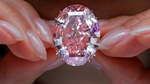 """FILE - In this Wednesday, March 29, 2017, file photo, the """"Pink Star"""" diamond, the most valuable cut diamond ever offered at auction, is displayed by a model at a Sotheby's auction room in Hong Kong. The stunning 59.6 carat diamond has sold for HK$553 million or US$71.2 million at a Sotheby's auction in Hong Kong, setting a record for any diamond or jewel. It's Also the highest price for any work ever sold at auction in Asia."""