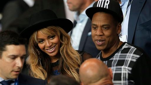 In a file photo, Beyonce and her husband Jay Z stand up at half time in the Champions League soccer match between PSG and Barcelona, at the Parc des Princes stadium, in Paris. Beyonce announced Monday that she is merging with British retailer Topshop to launch an exercise clothing company, Parkwood TopShop Athletic Ltd. The clothing line will be available next fall.