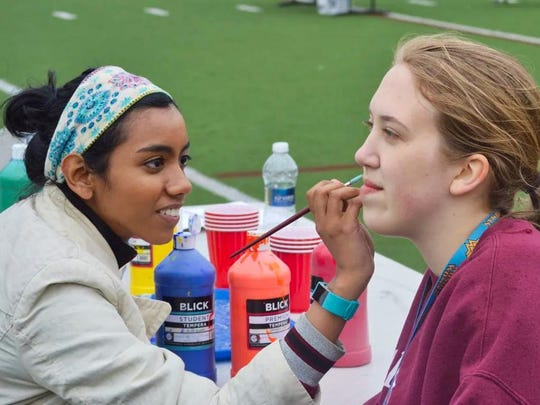 Caravel Academy Senior Nushi Mazumdar, left, paints junior Zoe Webb's face during Relay for Live.