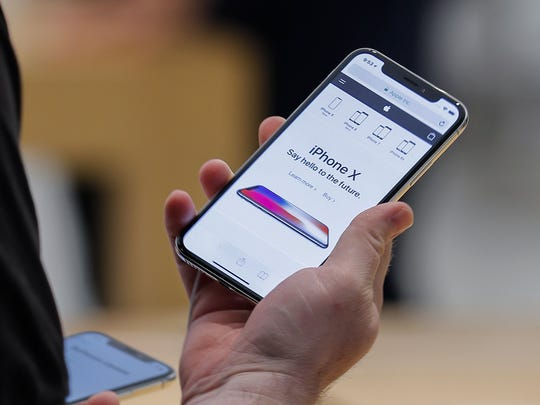 A customer examines the newly released iPhone X at an Apple Store in Atlanta,  Nov. 3 2017.