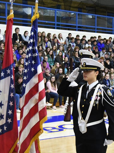 A member of the Mountain Home High School Navy Junior ROTC program salutes the American flag after posting it Thursday during the Freedom Is Not Free ceremony at The Hangar.