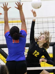Alamogordo's Claire Myers, right, spikes a ball Thursday night.