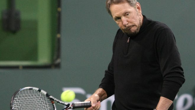 BNP Paribas Open owner Larry Ellison hits some balls with tennis legend John McEnroe before the start of a charity event at the Indian Wells Tennis Garden on March 1, 2014.