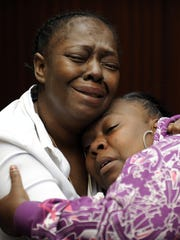 Grandmother Mertilla Jones, left, and aunt Lakrystal Sanders grieve for Aiyana Stanley-Jones, 7, who was killed in a 2010 raid, spurring protests.