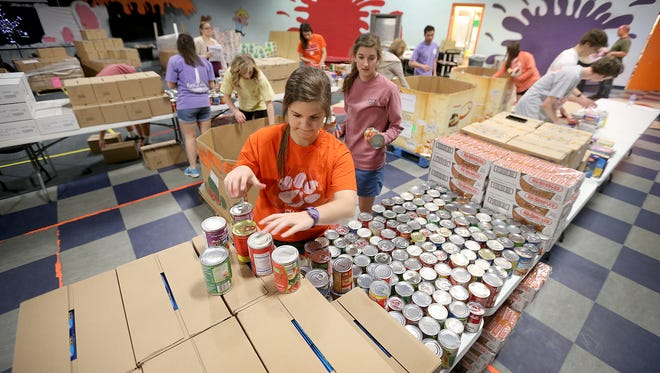 Clemson University students work on organizing tables of food at the Lakeview Church's food pantry Monday.