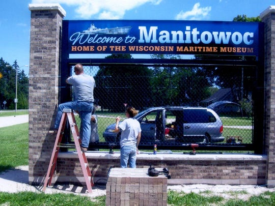 "E.F. Becker and Sons put the final piece on a ""Welcome to Manitowoc"" sign on Waldo Boulevard. Dean Becker, on ladder, Kim Becker, standing, Tim Becker, behind the sign, and Greg Becker furnished and installed the black chain-link panel and attached the organization logos."