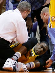 An injured Indiana Pacers' Ian Mahinmi, of France, is attended to by training staff during the first half of an NBA basketball game against the Phoenix Suns, Tuesday, Jan. 19, 2016, in Phoenix. (AP Photo/Ross D. Franklin)
