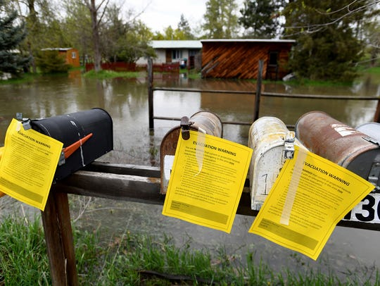 Evacuation warning notices hang on a row of mailboxes