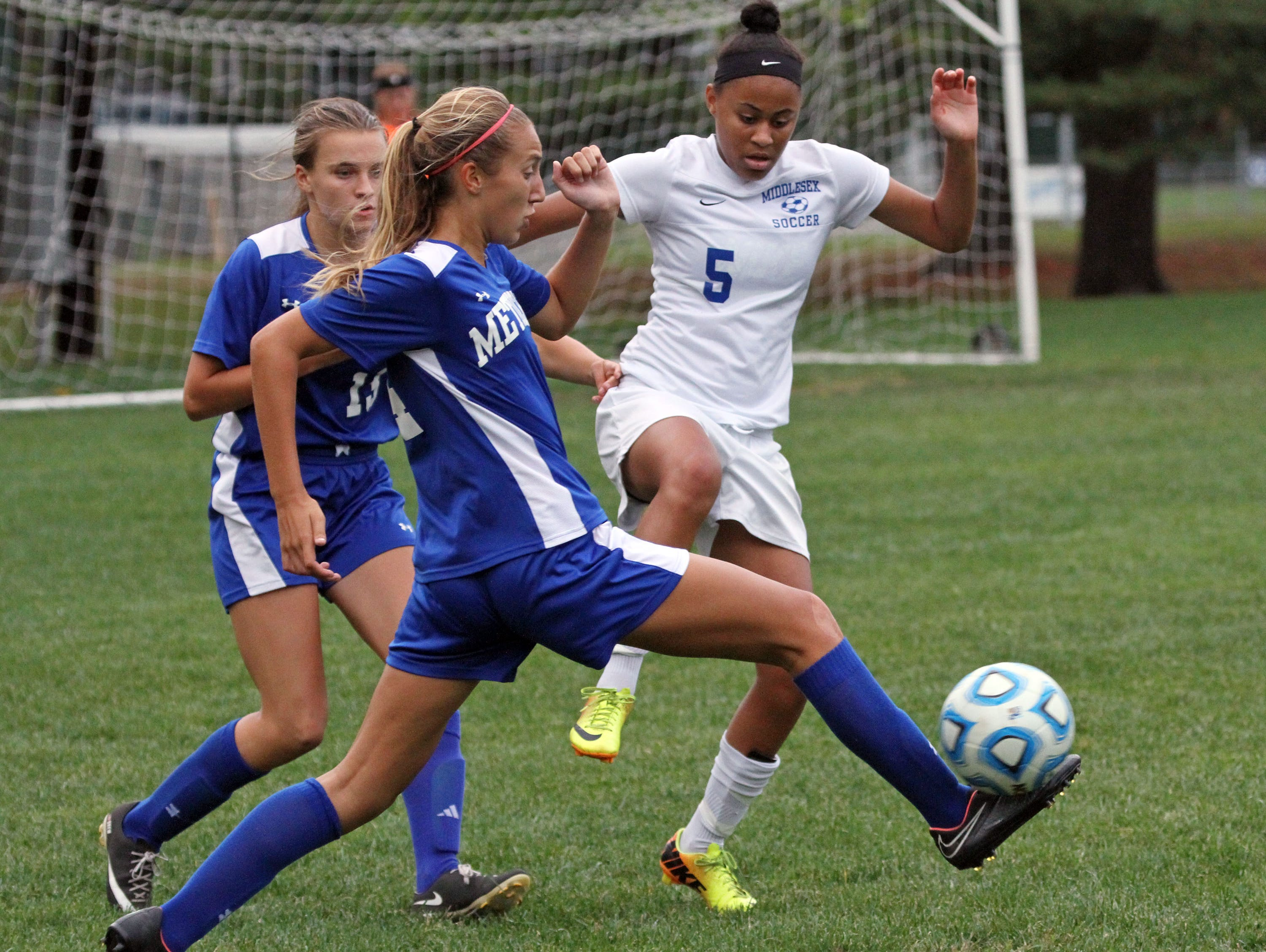 Metuchen's Hope Kenny boots the ball as Zakiya Beckles of Middlesex, right, challenges and teammate Drew Schuchman, left, watches, in girls soccer game at Middlesex.