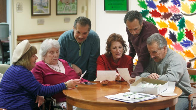 Members of the Oliveri family look over old photos during a visit with matriarch Maria Oliveri, 96, second from left, at St. Ann's Home. From left are niece Patty Oliveri Galante, Maria, Maria's son Carmelo Oliveri, daughter Josie Oliveri Cuva, son Tony Oliveri and son Joe Oliveri. The family came to America from Italy 60 years ago on Thanksgiving Day.