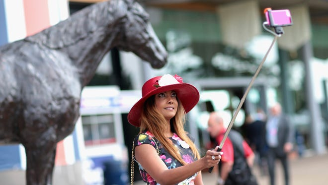 ASCOT, ENGLAND - JUNE 18:  A woman uses a selfie stick to take a photograph on Ladies Day on day 3 of Royal Ascot at Ascot Racecourse on June 18, 2015 in Ascot, England.  (Photo by Chris Jackson/Getty Images) ORG XMIT: 560082471 ORIG FILE ID: 477551942