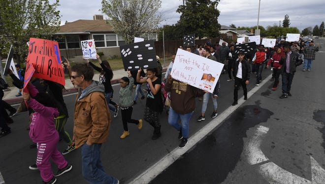 Marchers walk down Cross Avenue in Tulare to promote mental health awareness.