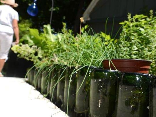 An innovative garden border featuring upended wine bottles at the Northville Township garden of Tamara Petonke.