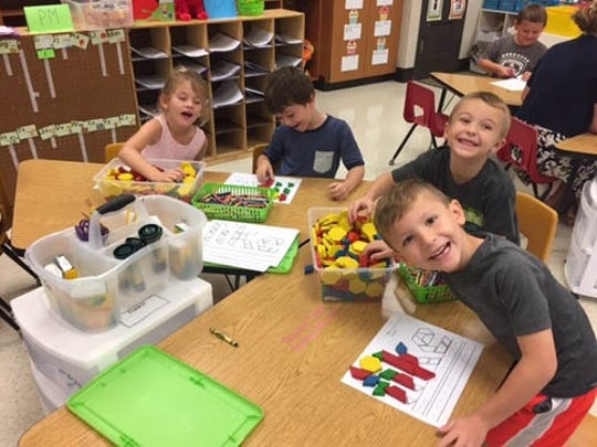 """Students in Carly Kleckner's kindergarten class at Dillsburg Elementary are working with """"like"""" tangrams and mental blocks. The students are practicing fine motor skills and sight word recognition as well as learning to take turns and think critically. Pictured are, from left, Allison Crist, Brenden Robel, Pat Coyne and Hayden Hennessey."""
