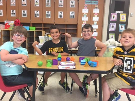 """Students in Carly Kleckner's kindergarten class at Dillsburg Elementary are working with """"like"""" tangrams and mental blocks. The students are practicing fine motor skills and sight word recognition as well as learning to take turns and think critically. Pictured are, from left, Ryder Yost, Edward Griffith, Lochlan Fitzgerald and Lucas Soliz."""