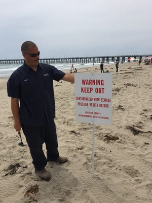 Rudy Camacho, a city of Oxnard employee, puts in a sign warning people at Hueneme Beach that the water had been contaminated by raw sewage.